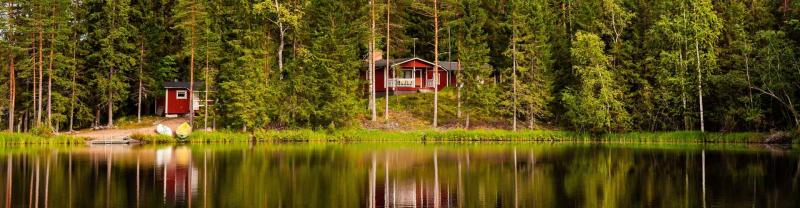 Red wooden cottages by the lake in rural Finland