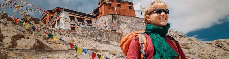 Traveller with backpack and sunglasses standing in front of Tibetan monastery and prayer flags