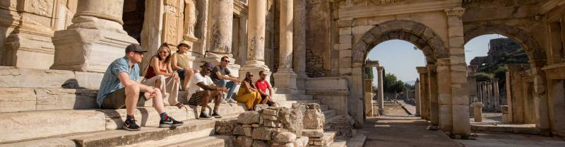 Travellers sit on the steps of Ephesus, Turkey