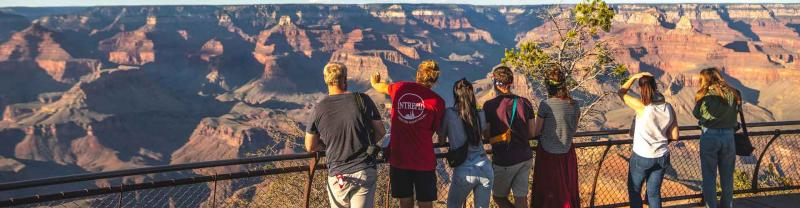 Group of travellers stand at lookout at the Grand Canyon