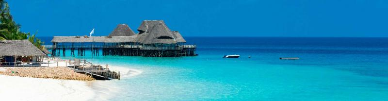thatched roof hut and pier into the crystal clear waters of Zanzibar