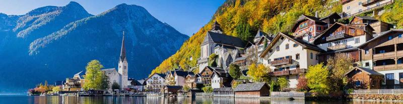 Houses and gothic church in the mountain village of Hallstatt, Austria, reflected on lake