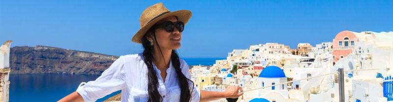 Woman stands in front of white buildings with blue domes by the sea in Santorini, Greece