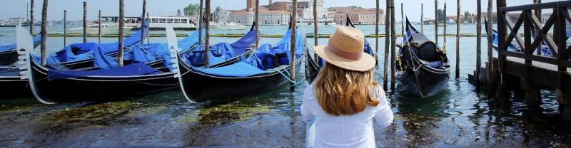 Traveller sitting on the banks of the canal looking at gondolas in Venice Italy