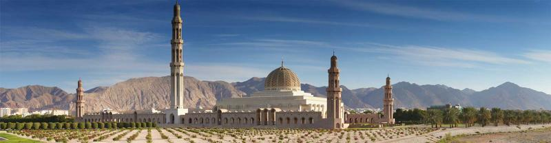 Wide view of the Grand Mosque in Muscat, Oman, with mountains in background