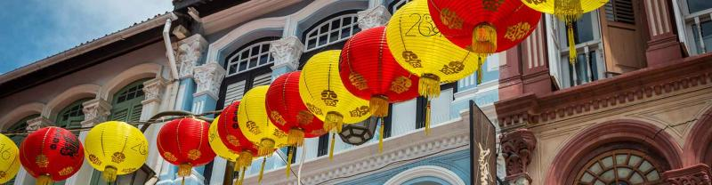 Red and yellow lanterns hang outside colourful buildings in Chinatown, Singapore