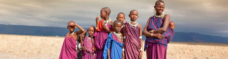 A masai family in traditional robes standing in the middle of the serengeti with mountain range in the background