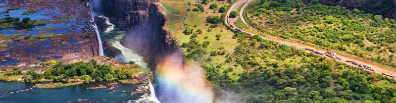 Rainbow forms on sunny day at victoria falls, zambia