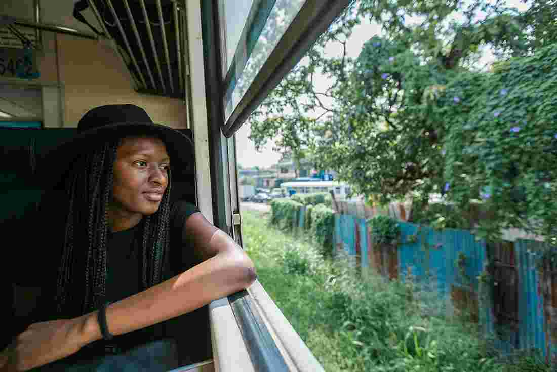 intrepid traveller looking out to the lush green landscape on her train journey in sri lanka