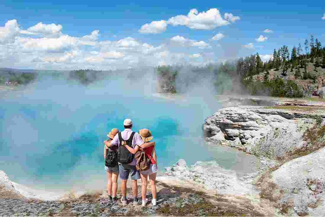 Family admiring geyser in Yellowstone National Park, Wyoming, USA