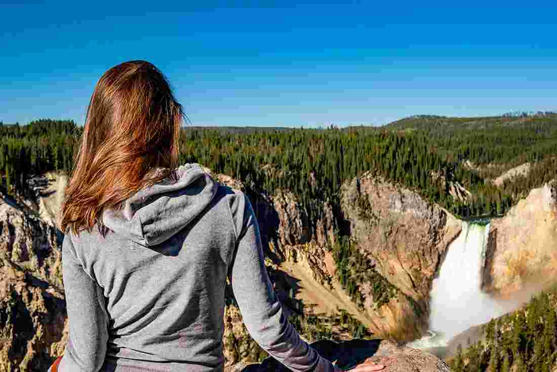 SASY - Tourist looking over waterfall in Yellowstone National Park