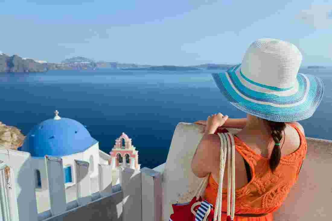Traveller looking over the blue water of Santorini in Greece