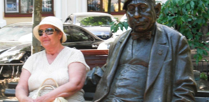 lady sitting next to a statue