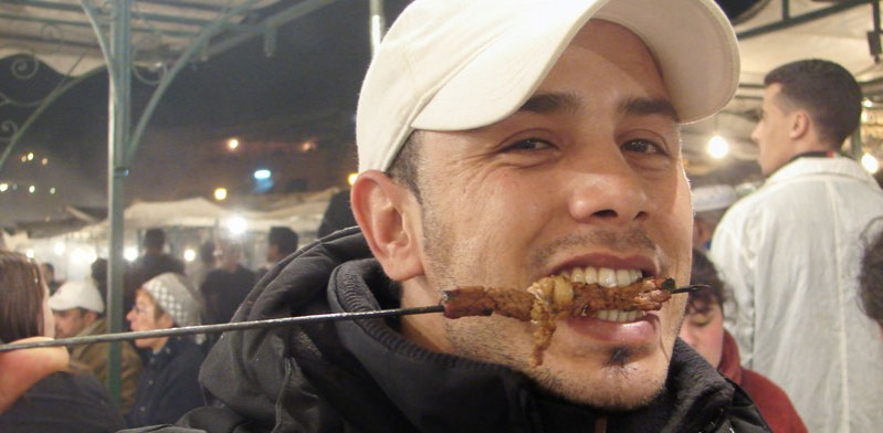 male traveller eating a shish kabob in morocco