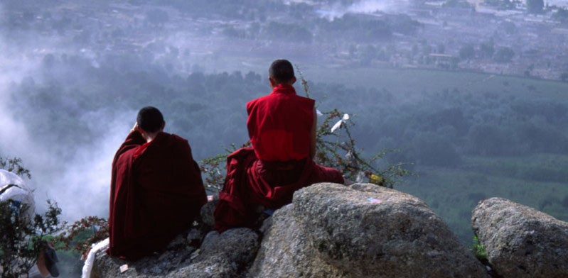 two tibetan monks overlooking a mountain view