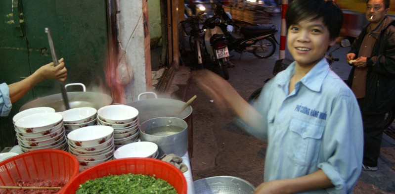 chef cooking vietnamese food in hanoi street