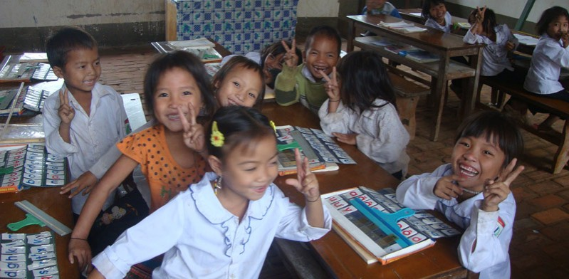 children in a classroom giving a peace sign