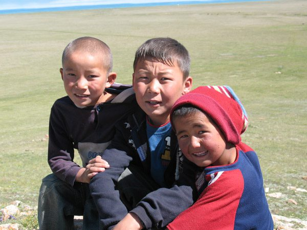 Local Kyrgyz children join in a walk around the lake