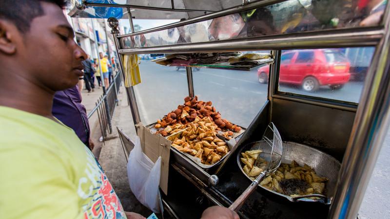 A street vendor deep fries Sri Lankan snacks
